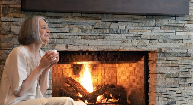 Lady enjoying cup of tea by fireplace